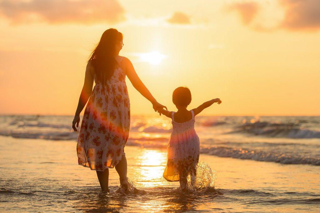 mère et enfant sur une plage oubliant les aspects ennuyeux